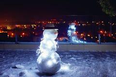 在屋顶大阳台,城市背景的逗人喜爱的雪人 免版税库存照片