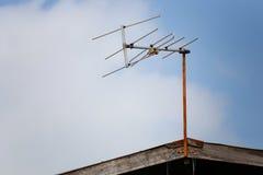 在屋顶房子的老电视塔 库存图片