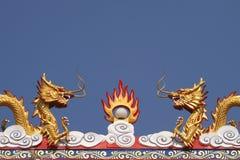 在屋顶的两个中国龙雕塑在蓝天背景中 库存图片