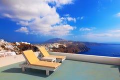 在屋顶的两deckchairs 大厦希腊小山海岛santorini 免版税库存照片
