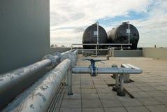 在屋顶的储水箱与管道线路 免版税库存照片