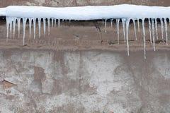 在屋顶的冰柱 葡萄酒破旧的墙壁背景 冷的冬天天气概念 软绵绵地集中 免版税库存照片