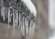在屋顶的冻结的融化水冰柱, 图库摄影