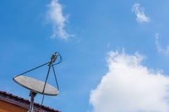 在屋顶的卫星盘有美好的蓝天背景 免版税库存照片