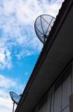 在屋顶的双卫星盘有美丽的蓝天的 图库摄影