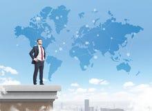 在屋顶的商业领袖与世界地图 免版税库存图片