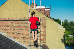 在屋顶的妇女上升的梯子 免版税库存图片