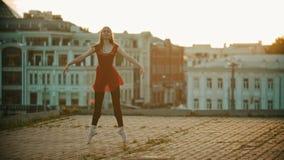 在屋顶的年轻微笑的妇女芭蕾舞女演员训练-站立在她的脚尖和显示舞蹈元素 股票视频