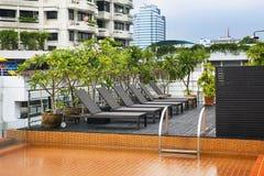 在屋顶的橙色游泳池与现代大厦。 图库摄影