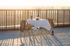 在屋顶的浪漫晚餐在日落 免版税库存照片