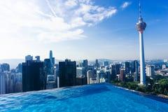 在屋顶的游泳池与吉隆坡美好的都市风景  免版税库存图片