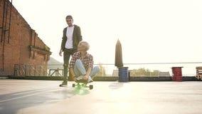 在屋顶的滑板获得乐趣被推挤的行家女孩与她的男朋友在日落 人英俊的年轻人 影视素材