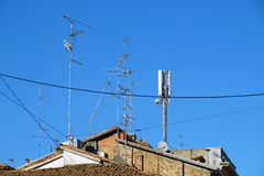 在屋顶的电视天线有蓝天的 免版税库存照片