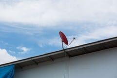 在屋顶的红色卫星盘有美丽的蓝天的 免版税图库摄影