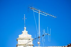 在屋顶的老白色电视天线有蓝天的 免版税库存图片