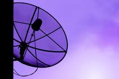 在屋顶的通讯卫星盘有日落天空backgro的 免版税库存照片