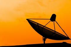 在屋顶的通讯卫星盘有日落天空backgro的 库存图片