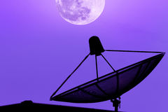 在屋顶的通讯卫星盘有supermoon天空后面的 库存照片