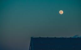 在屋顶的满月在微明 库存照片
