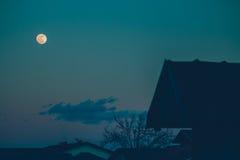 在屋顶的满月 免版税库存图片