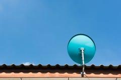 在屋顶的绿色卫星盘有美丽的蓝天的 免版税图库摄影