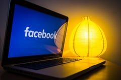 在屏幕上的新的facebook商标,起动光在背景中 免版税图库摄影