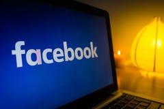 在屏幕上的新的facebook商标,起动光在背景中 免版税库存照片
