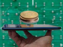 在屏幕上的智能手机在堆Bitcoins中 免版税库存图片
