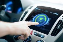 在屏幕上的男性手设置汽车eco系统模式 免版税库存照片