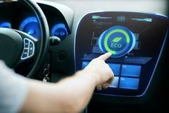 在屏幕上的男性手设置汽车eco系统模式 免版税库存图片