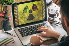 在屏幕上的辐射标志,工作在办公室的人 免版税库存图片