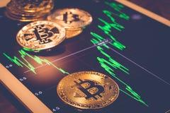 在屏幕展示绿色上升性能图的Bitcoins 库存图片