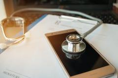 在屏幕片剂,在医学医生的便携式计算机的听诊器 库存图片