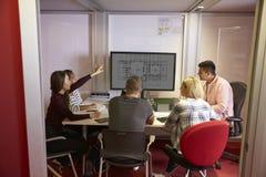 在屏幕附近的学生合作在项目的小组  库存图片