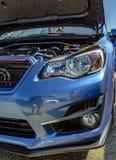 在展示的发动机元件在有敞篷的一辆蓝色汽车流行了 图库摄影
