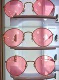 在展览架的五颜六色的桃红色太阳镜 图库摄影