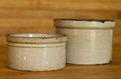 在屠户委员会桌上的两个小黏土缸 免版税库存照片