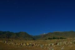 在山、夜和星的老石头 免版税库存照片