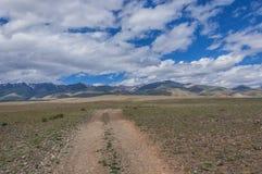在山、天空和云彩背景的一个土路干草原  免版税图库摄影