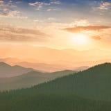 在山、小山、太阳和天空的五颜六色的日落 免版税库存照片