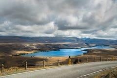 在山、特卡波湖和剧烈的多云天空,北岛新西兰的路 免版税库存照片