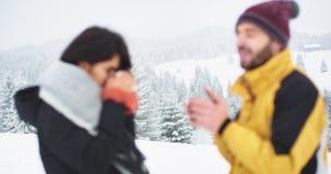 在山上面与惊人的风景两游人的结冰,设法得到温暖他们喝某一热的饮料从 股票视频