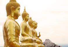 在山上面的四个金黄菩萨雕象 免版税库存图片