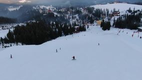 在山下的一个长的多雪的倾斜与许多人滑雪和雪板运动,在小山下的美好的手段,空中 股票视频