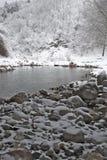 在山下的冬天河 免版税库存照片