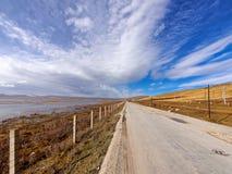 在山中的平直的乡下公路和湖有美好的多云天空背景在gahai国家级自然保护区公园 库存照片