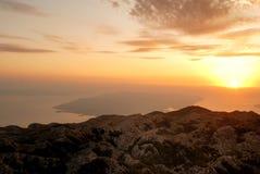 在山之上的日落与距离的海岛 免版税库存照片