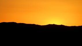 在山之后的日落 免版税库存照片