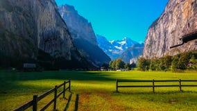 在山之间的村庄与绿色草甸 库存照片