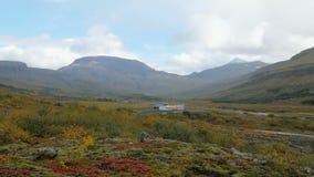 在山之间的美妙的河边低地在冰岛,红色,黄色和绿草在多云秋天天 股票视频